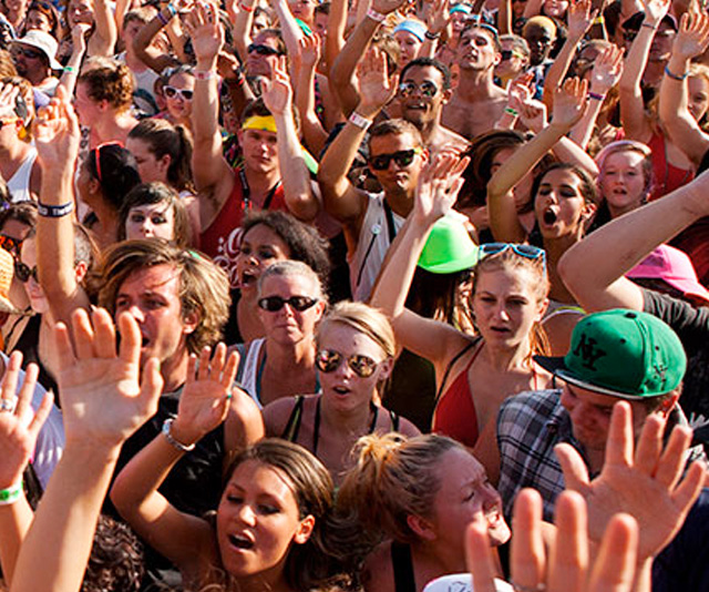 Large crowd with hands raised at a music and beer event in DC