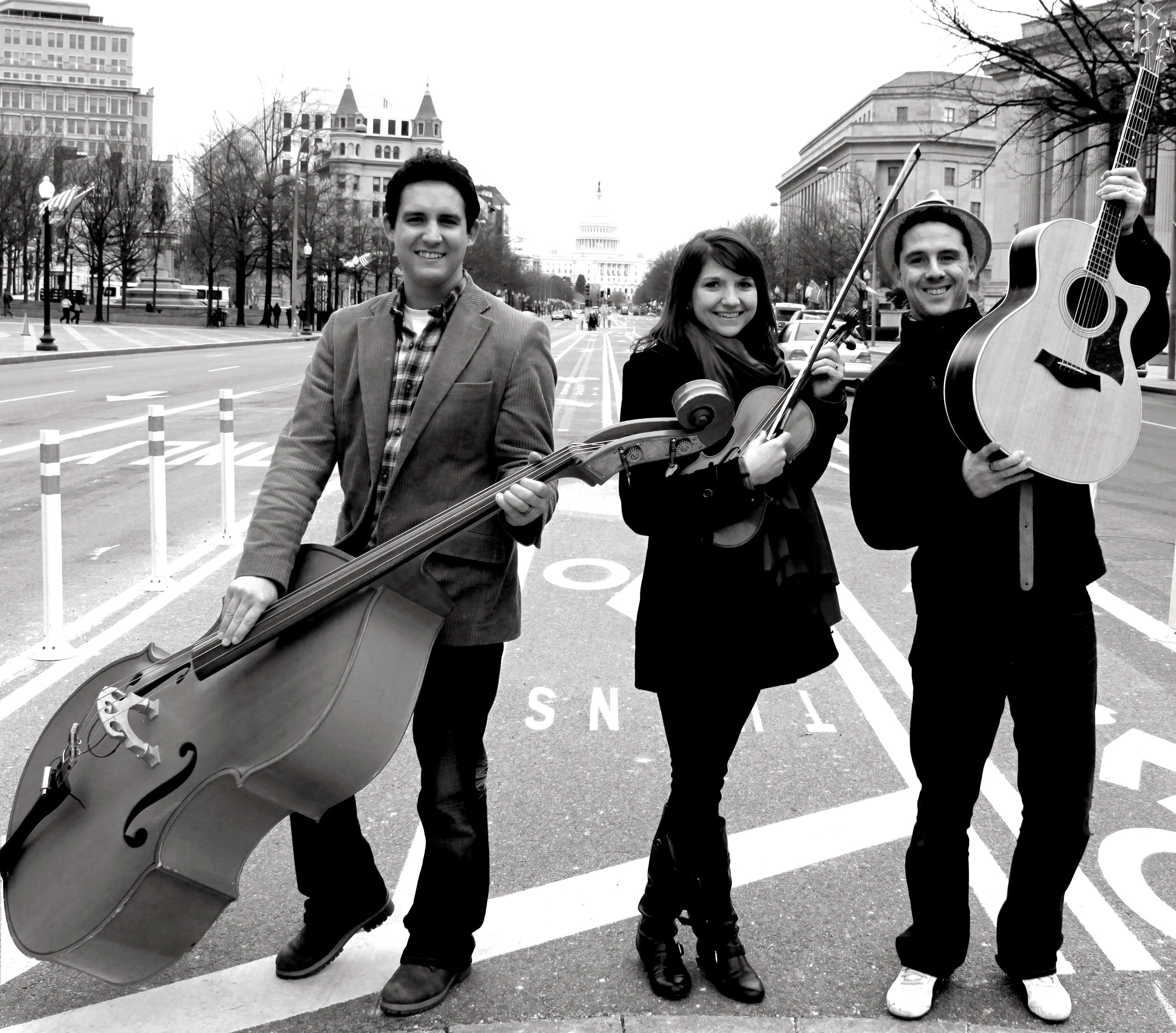 The 19th Street band trio with bass, violin, and guitar standing in DC street
