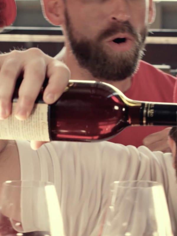 Fan in baseball gear pouring wine with friends