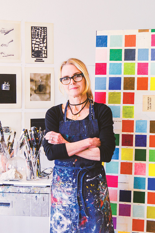 Artist Julie Wolfe in a paint covered smock posing in her studio