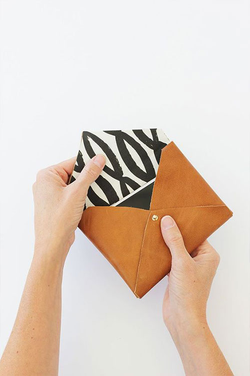 Opening a handcrafted leather pouch from a DIY class in DC