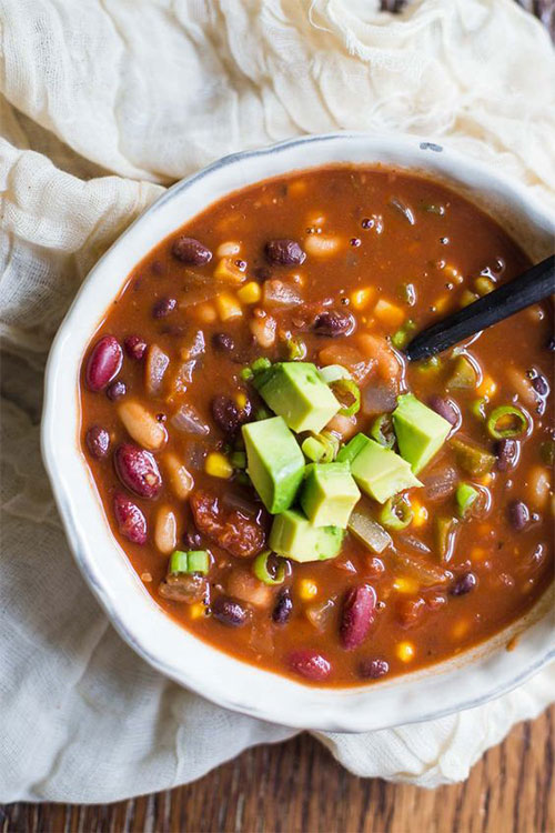 Bowl of vegetarian chili topped with fresh avocado