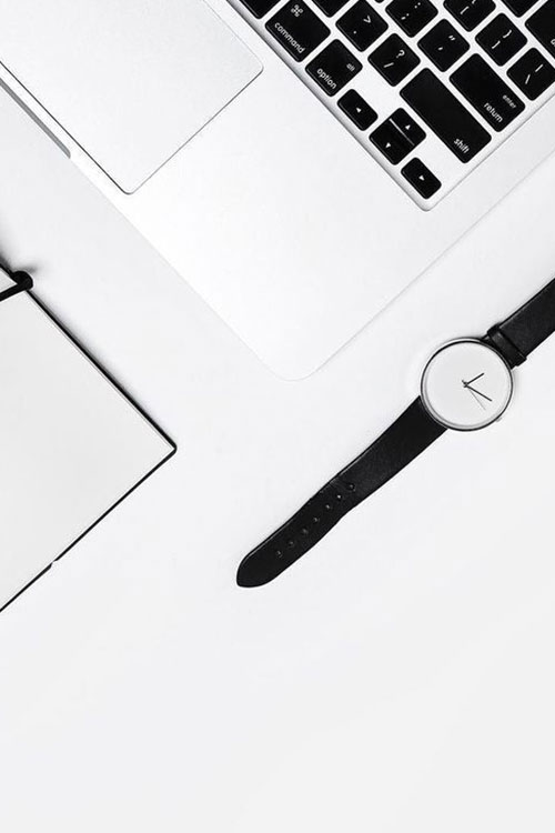 Black and white watch, notebook, and laptop
