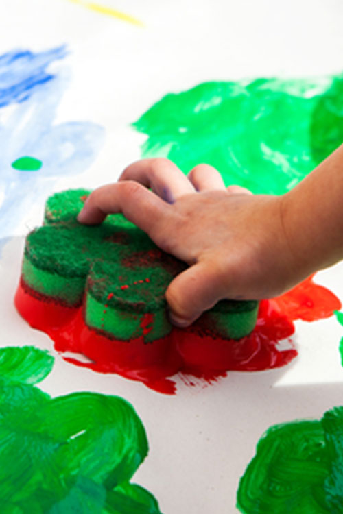Child creating their own wrapping paper with sponge painting
