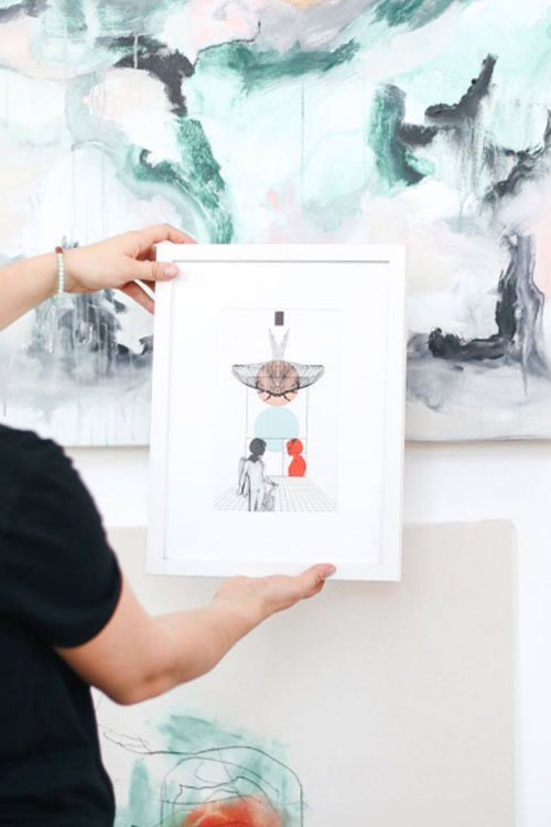 Woman holding framed illustration at an art event in DC