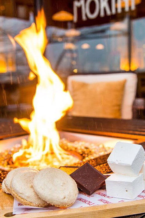 S'mores ingredients sitting by a fire pit during an event on the waterfront