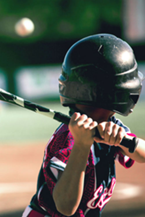 Child in baseball helmet swinging a bat