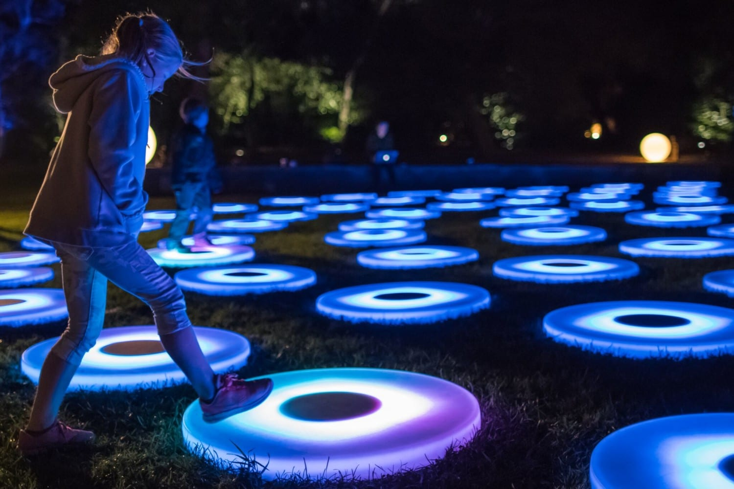 Child playing on interactive glowing light ornaments at night