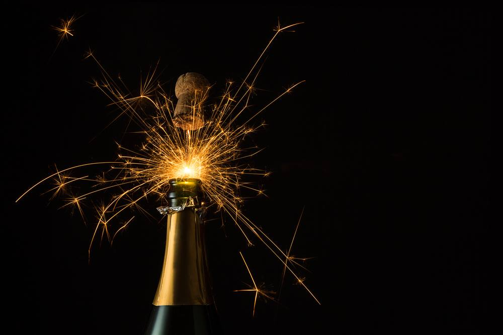 Fireworks popping the cork out of a champagne bottle