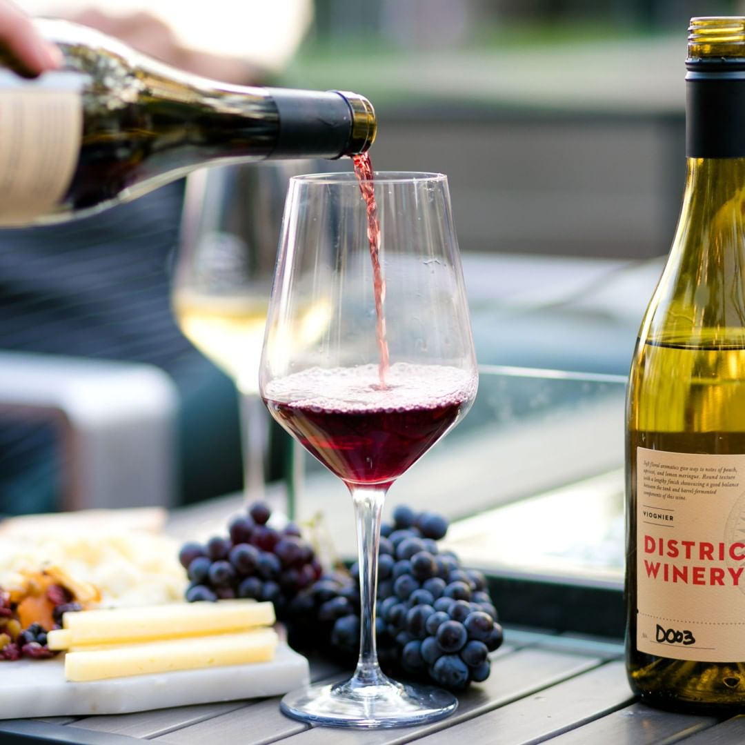 Red wine from District winery being poured into a glass, bottle of Viognier, red grapes and cheese sit to the side