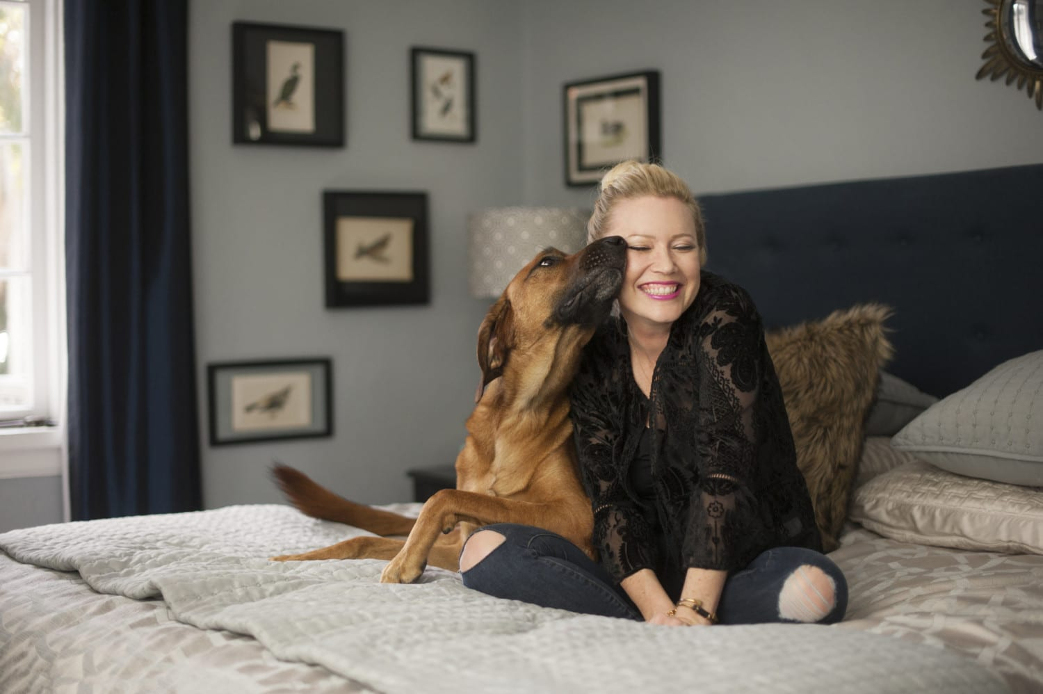 A woman and her dog on a bed