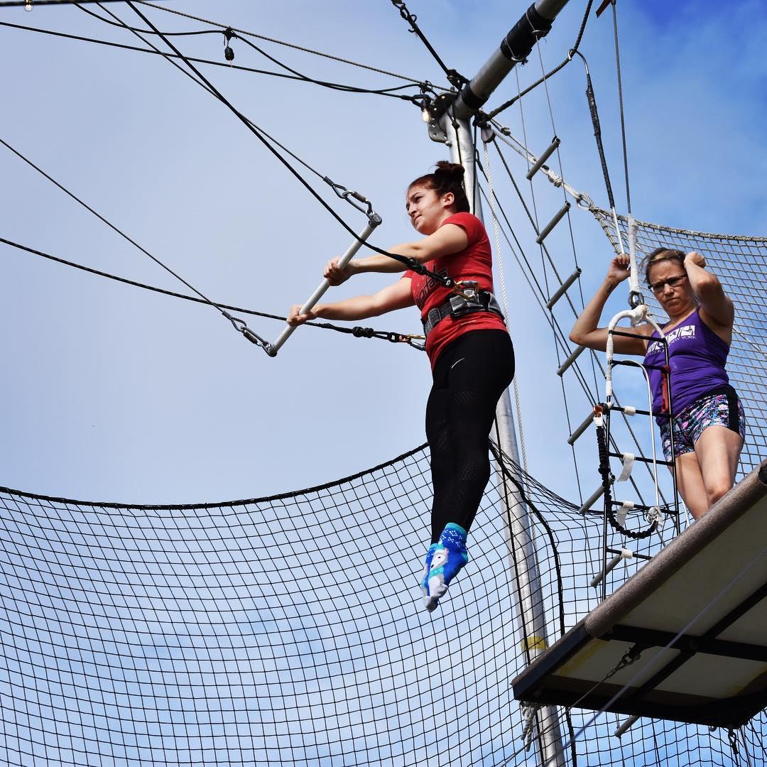 Woman in a harness on a trapeze course