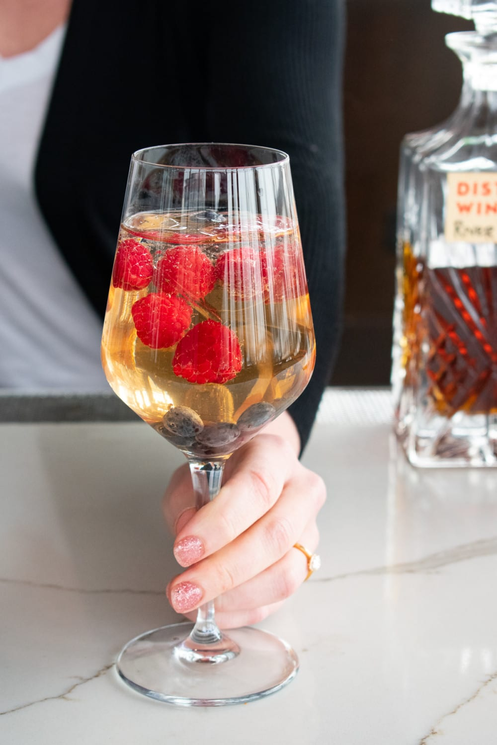Woman holding sparkling wine topped with fresh fruit at District Winery
