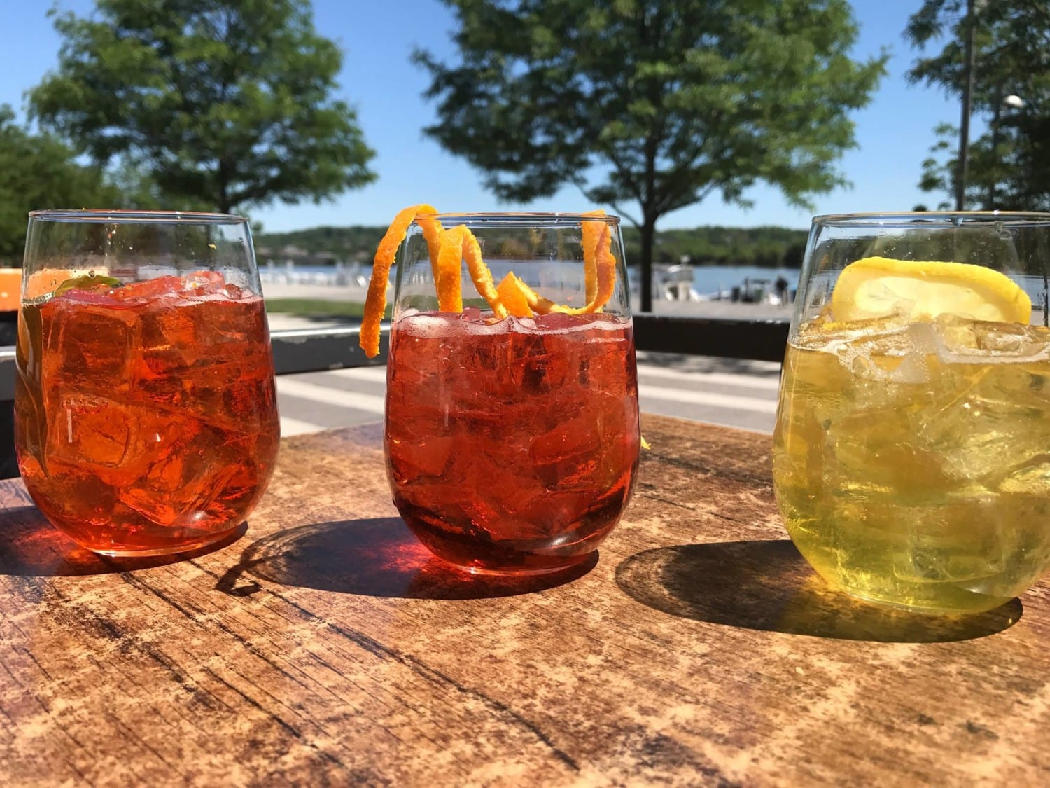 Three cocktail glasses garnished with fruit on open air table by the water