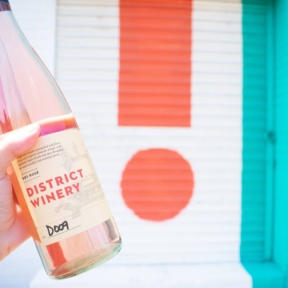Hand holding bottle of dry Rosé wine from District Winery