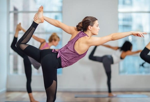 Woman doing bow pulling pose in a female yoga class