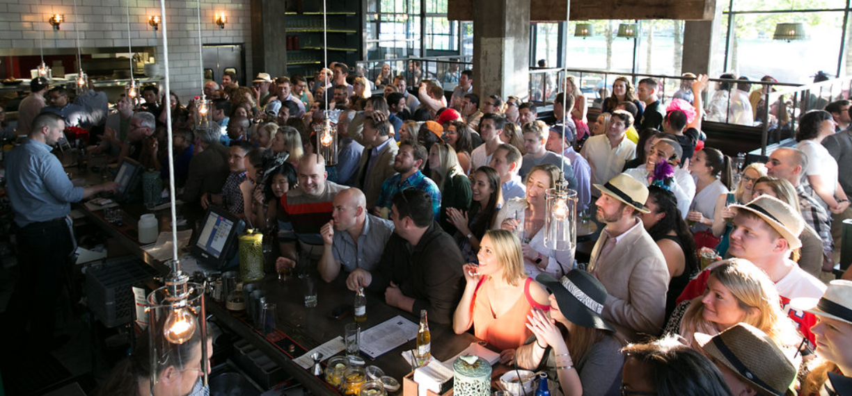 Crowded sports bar patrons watch tv during a summer event