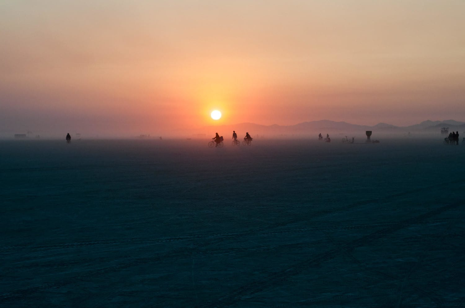 A sunset in the mountainous landscape of the Black Rock Desert, Nevada behind several bike riders.