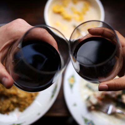 Two people toasting with red wine